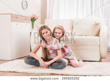 Two young cuties sitting on the floor in lovely embrace
