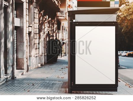 A Poster Placeholder Inside Of City Bus Stop Near The Road; Vertical Blank Advertising Banner Mock-u