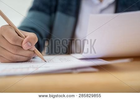 Education Test Concept : Hands With Blue Pen Over Application Form, Students Taking Exams, Writing E