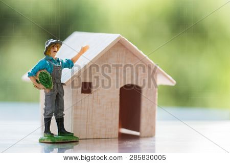 Agriculture Gradening Concept : Miniature Farmer People Standing Near Wooden Home On Green Backgroun