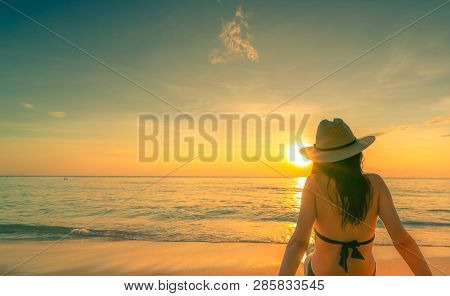 Back View Of Asian Woman Wear Bikini And Straw Hat Sit On Sand Beach Relax And Enjoy Holiday At Trop