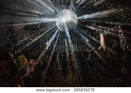 A Big Disco Ball Is Hanging From The Ceiling. A Lot Of People Are Dancing On The Background.