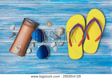 7b34b959f Top view on mock-up of white paper card with bottle of sunscreen and  seashells on blue wooden background