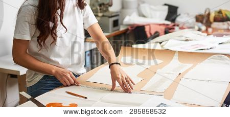 Workplace In Design Studio. Professional Female Designer Making Paper Patterns Using Measuring Tape,