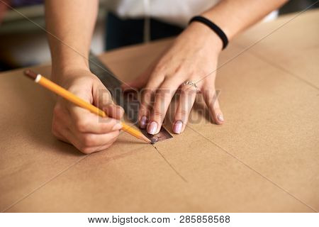 Work Place In Design Studio. Professional Female Designer Hands Close-up Making Paper Patterns Using