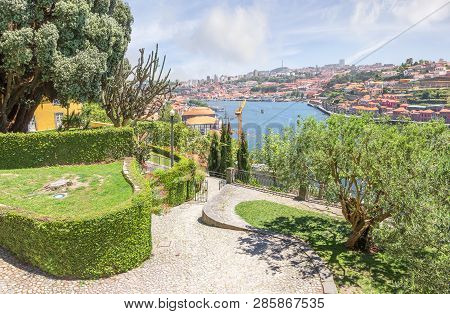 Porto, Portugal - June 16, 2018:  View Of The Douro River And Walking Alleys Of Park From The Crista