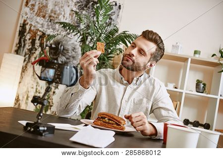Sandwich Ingredients. Portrait Of Male Bearded Blogger Tasting A Food While Recording New Video For