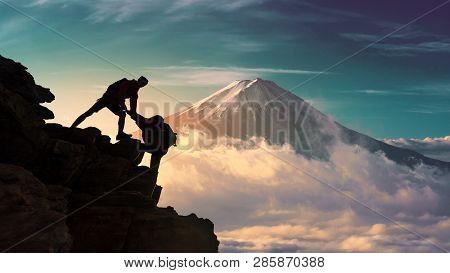 Young Asian Couple Hikers Climbing Up On The Peak Of Mountain Near Mountain Fuji .climbing ,helps An