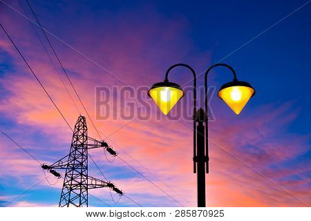lit on streetlamp at sunset with high-tension line and pylon on the background poster