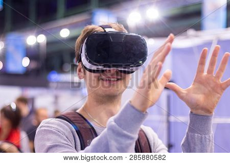 Young Man Is Using Virtual Reality Glasses On An Expo