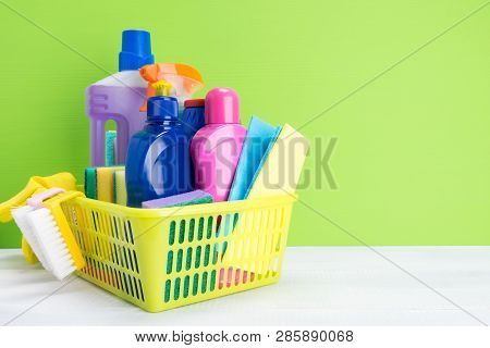 Set Of Cleaning Products And Detergents For Cleaning In A Yellow Basket On A Green Background, A Pla