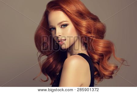 Beautiful Model Girl With Long Curly Red Hair . Styling Hairstyles Curls .wavy Shiny Care