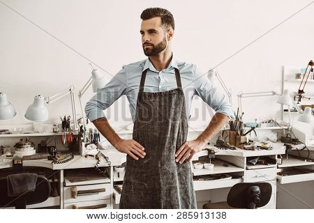 Future Plans. Portrait Of Confident Male Jeweler In Apron Putting Hands On Hips While Standing At Hi