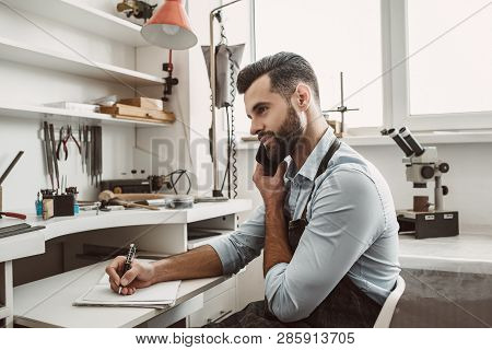 Important Conversation With Customer. Young Bearded Jeweler Is Talking With Customer By Phone And Ma