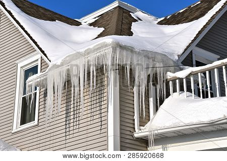 Massive Icicles Hang From A House With A Snow Covered Roof After A Winter Storm.