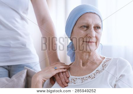 Daughter Supporting Senior Woman Wearing Blue Headscarf, Suffering From Lung Cancer
