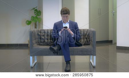 Young Fashionable Businessman Using Smartphone Texting Message Sitting On The Sofa. Caucasian Young