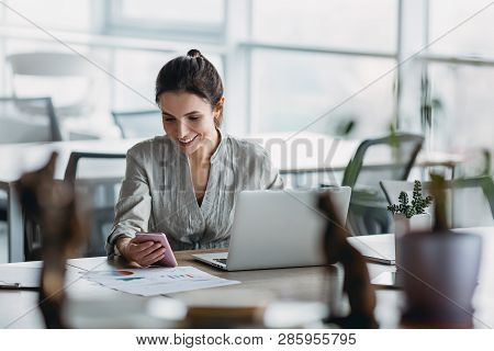 Young Business Woman On The Phone At Office. Business Woman Texting On The Phone. Pretty Young Busin