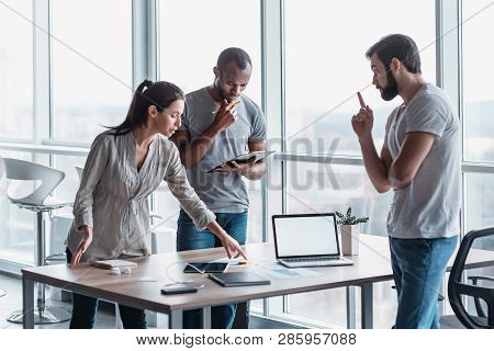 Diverse Group Of Focused Colleagues Discussing Business Strategy Together During A Meeting In An Off