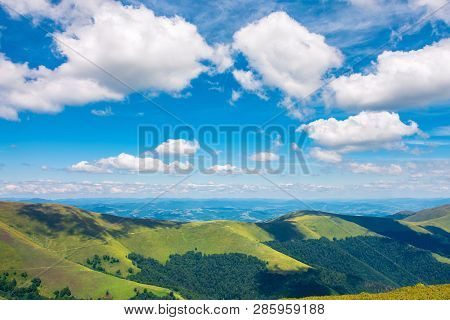 Fluffy Clouds Above The Mountain Ridge. Wonderful Summer Scenery With Grassy Alpine Meadow. Beautifu