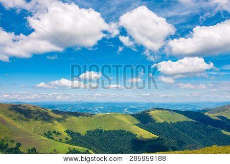 Fluffy Clouds Above The Mountain Ridge. Wonderful Summer Scenery With Grassy Alpine Meadow. Beautifu