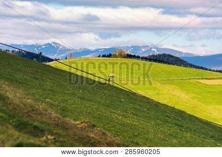 Rural Field On Grassy Hill In Mountains. Distant Ridge With Snowy Tops. Beautiful Countryside Scener