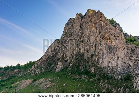 Beautiful Nature Of Romania Mountains. Springtime Landscape At Sunrise. Cliff In Shade Beneath A Blu