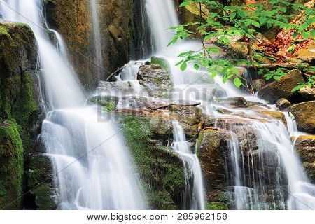 Waterfall With Small Cascades. Beautiful Nature Background In Summer. Branch With Green Leaves Above