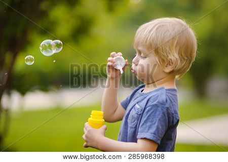 Cute Little Boy Blowing Soap Bubbles In Beautiful Summer Park. Active Leisure For Toddler Child