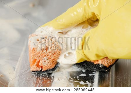 Detergent Cleaning Foam On Gas Stove Surface Close-up. Hand In Yellow Glove Clean Dirty Kitchen Cook
