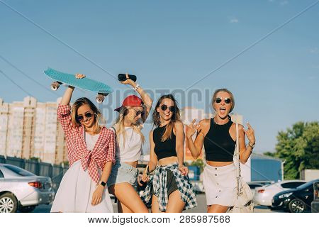 Four Young Girls Have Fun At The Car Park.