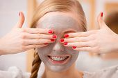 Facial dry skin and body care, complexion treatment at home concept. Happy young woman having grey mud mask on her face hiding eyes. poster