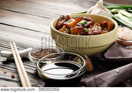 Crispy Stir Fried Tofu Cubes With Chives In Clay Dish On Wooden Kitchen Table With Napkin Chives Pep