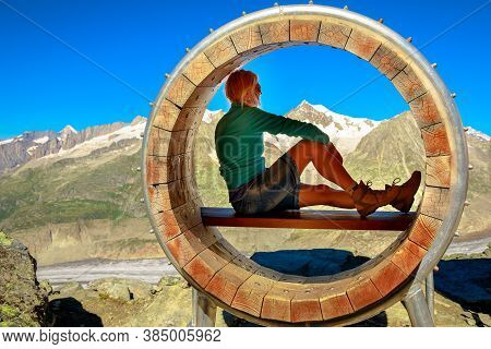 Hiker Woman Relaxing Inside Wood Bench After Trekking In Swiss Bernese Alps Mountain Range, Valais C