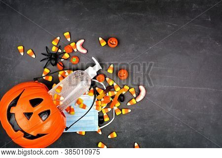 Halloween Jack O Lantern Pail With Spilling Candy And Coronavirus Prevention Supplies. Above View Ov