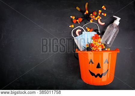 Halloween Jack O Lantern Pail With Spilling Candy And Covid 19 Prevention Supplies. Top View Over A