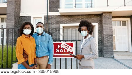 African American Young Happy Married Couple In Medical Masks Standing Outdoor At New House With Fema