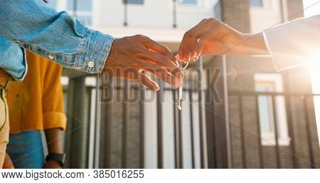 Close Up Of African American Female Hand Passing Key To Male Outdoors In Sunlight. Woman Handing Key