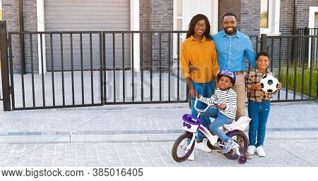 Portrait Of Happy African American Family With Small Children Standing At Street Near House At Subur