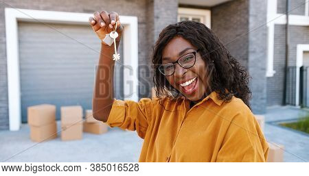 Portrait Of Cheerful Happy African American Woman In Glasses Smiling To Camera And Showing Key To Ca