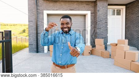 Portrait Of Cheerful Happy African American Man Smiling To Camera And Showing Key To Camera While Mo