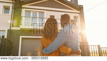 Rear On African American Young Just-married Couple Standing At Yard Of House, Hugging And Observing
