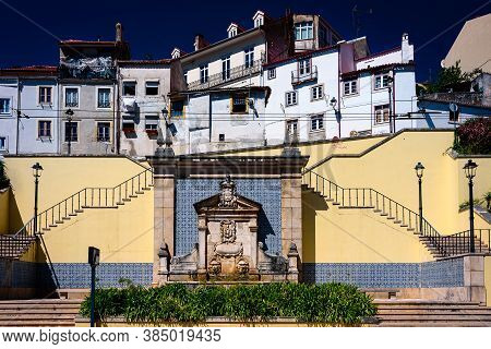 Architectural Detail In Coimbra: Fountain On Wall. Old Houses At The Top Of A Fountain In Coimbra, P