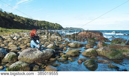 Redhead Young Woman Sitting On A Rock And Enjoying The Sea Breeze On The Baltic Seashore, On Rugen I