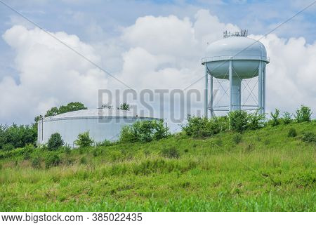 Horizontal Shot Of A Municipal Water Tower Against A Blue Cloudy Sky.