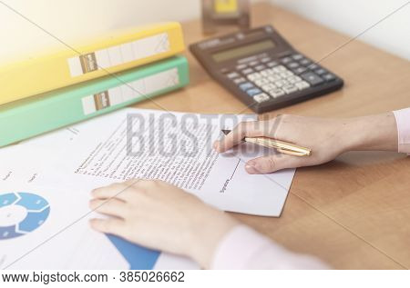 Businesswoman Is Signing A Contract At Office Table With Folders, Stamp And Contract, Signing Agreem