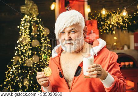 Christmas For Modern Santa Claus. Santa Make Funny Face And Picking Cookie. Santa Claus Eating Cooki