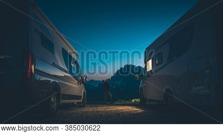 Caucasian Men In His 40s With Head Mounted Flashlight Between Two Camper Vans. High Mountains Campin