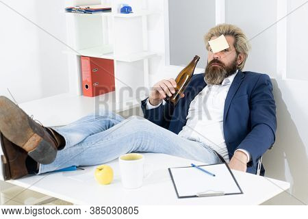 Bored Drunk Businessman In Office At End Of The Work Day. Business Man Drinking From Stress