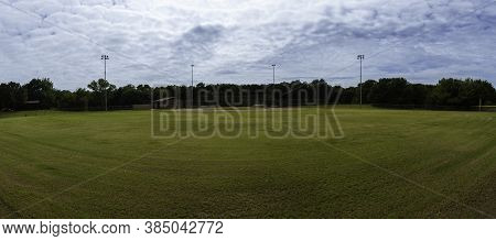 A Panoramic View Of An Empty Baseball Field In A City Park Looking Toward Home Base From Centerfield